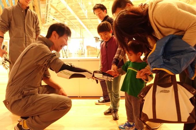 文化庁メディア芸術祭富山展「トヤマウォーカー」デモンストレーションで子どもと握手をする森川さん  photo by exiii