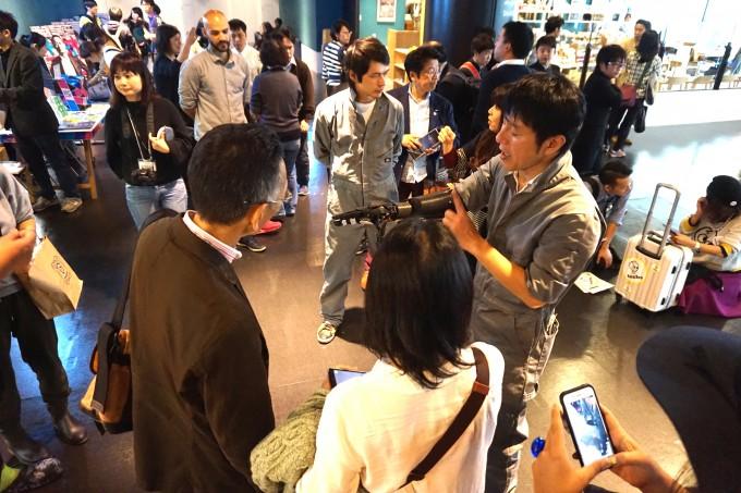 【写真】たくさんの人がいる中でハンディーの説明をしているイクシーのメンバー