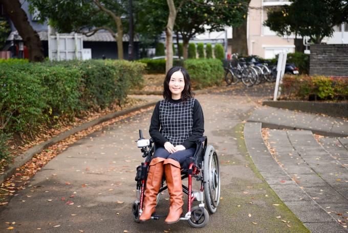 【写真】車椅子に乗り街頭で微笑むおだゆりこさん