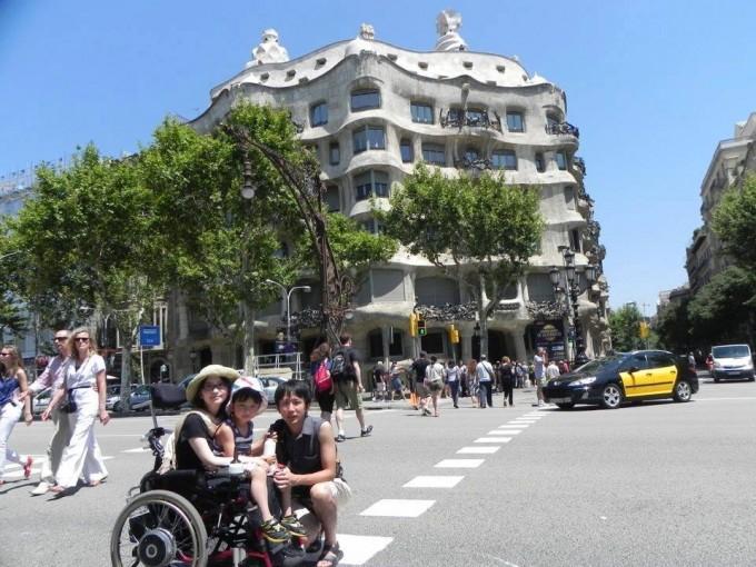 【写真】日差しがさしているバルセロナで車椅子に乗ってえいいちくんを抱いているゆりこさんとよういちさん。