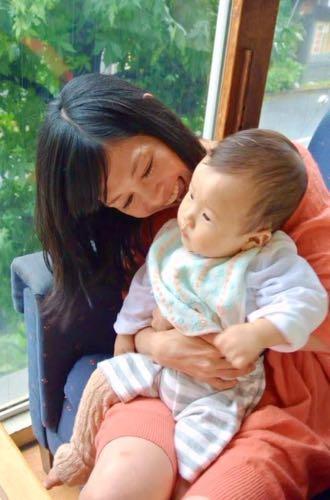 【写真】児童精神科医をしていた頃のいぶきさん。赤ん坊を抱いて笑顔で話しかけている。