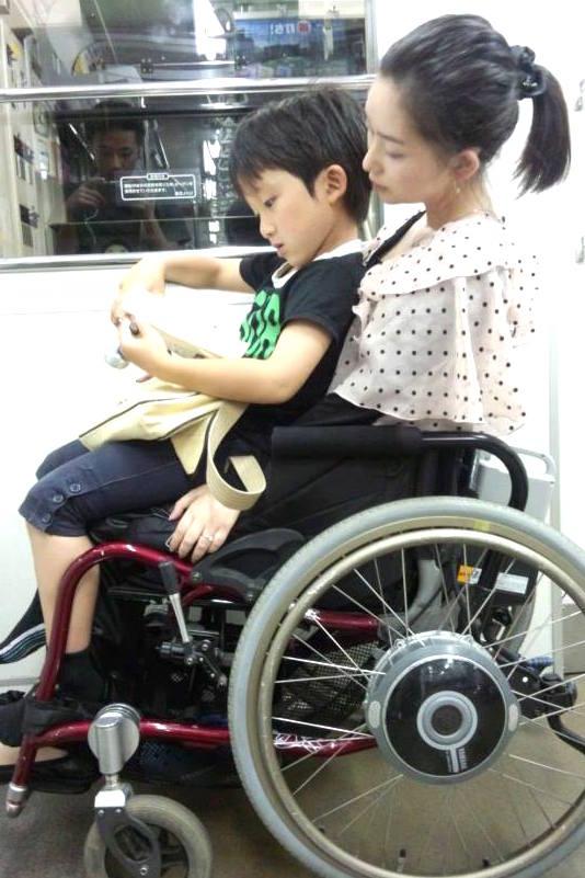 栄一くんを抱いて電車に乗る友理子さん