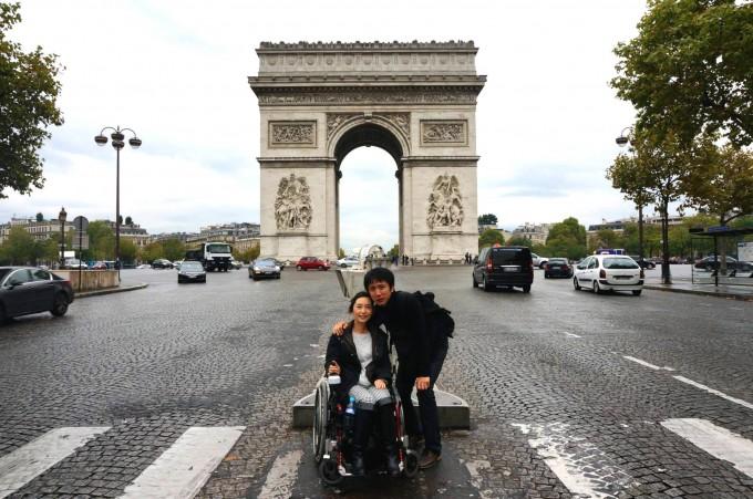 【写真】フランスの凱旋門の前でのゆりこさんとよういちさん。よういちさんがゆりこさんに寄り添っている