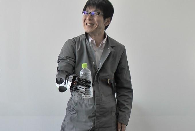 【写真】ハンディーをつけて笑顔でペットボトルをもつもりかわあきらさん
