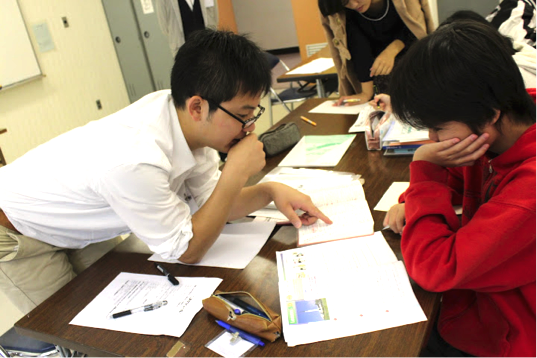 【写真】スリーキーズでの学習支援の風景。机を挟んで子供に勉強を教えている。