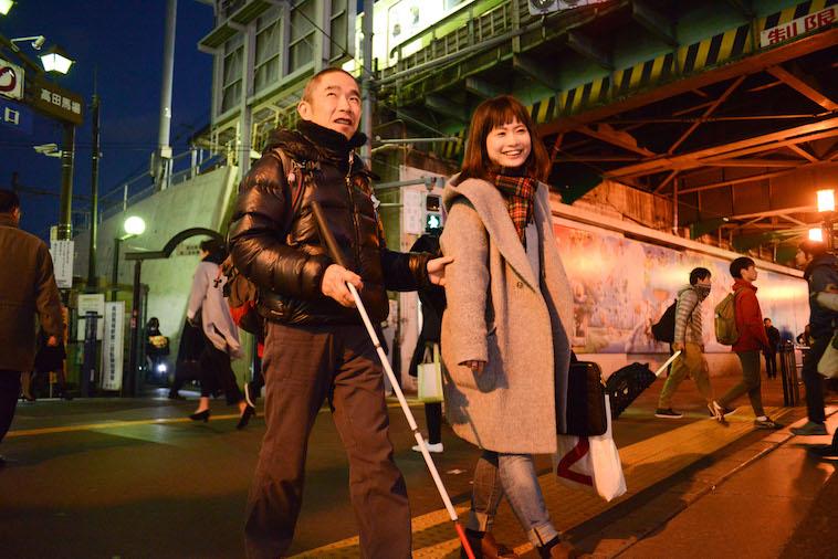 【写真】白杖を持って歩くこばやしこういちろうさんとライターのくどうみずほ