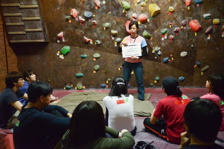 【写真】講習の様子。参加者は講習を体育座りをして真剣に聞いている。