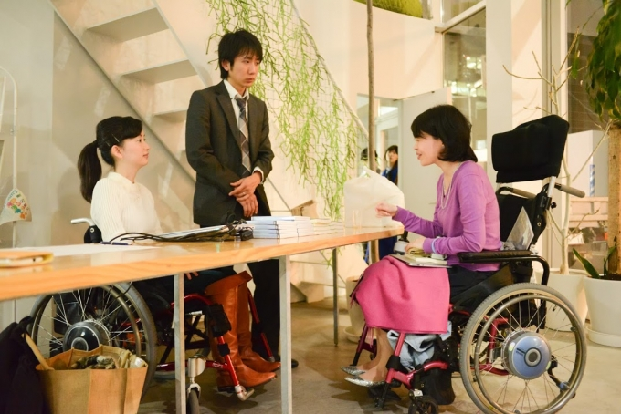 【写真】車椅子に乗る参加者の方と話をするおださんと旦那さんのよういちさん。