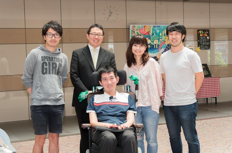 【写真】微笑みながら車椅子に座っているおんださとしさんとさかたさん、ライターのくどうみずほ