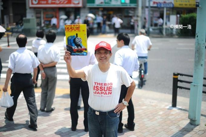 【写真】びっぐいしゅーの雑誌を右手に掲げて笑顔で道にたたずむびっぐいしゅーの販売員