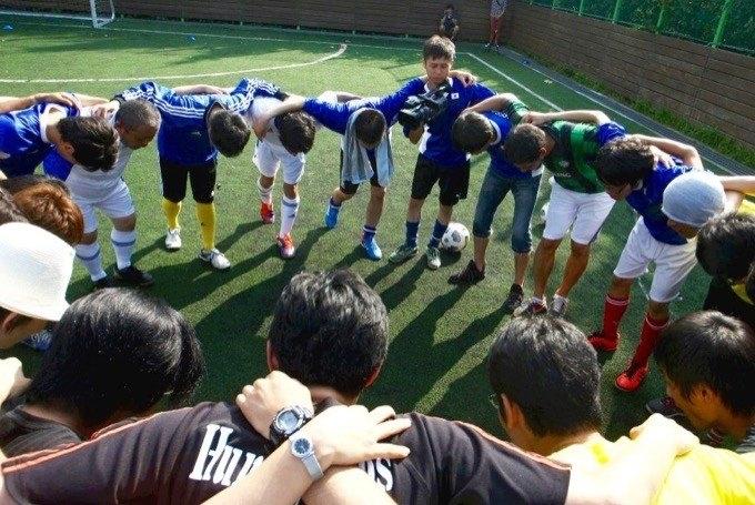 【写真】サッカーのユニフォームを着て大きい円陣を組んでいるチームメンバー