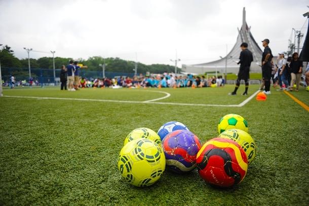 【写真】コートのうえに並べられたサッカーボール。奥では子供たちが座ってコーチの話を聞いている。