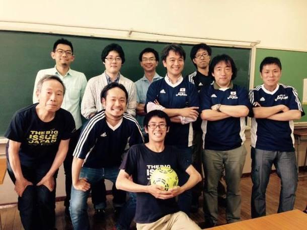 【写真】黒板の前で笑顔でカメラを見つめる人たち。スポーツのユニフォームを着ている人や手にサッカーボールを持っている人もいる。