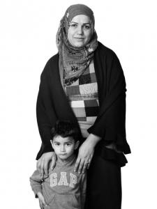 【写真】頭にスカーフを巻いた母と子供。母は子供の肩に優しく手を置いている。