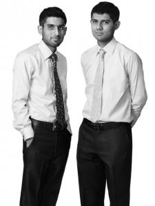 【写真】難民の青年二人がスーツを着てまっすぐにカメラを見つめている。