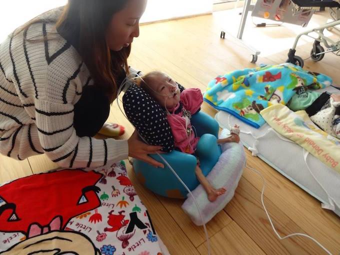 【写真】お母さんが家で、小さな子どもが座っている椅子を支えている。子どもの鼻や口には医療の管が繋がれている