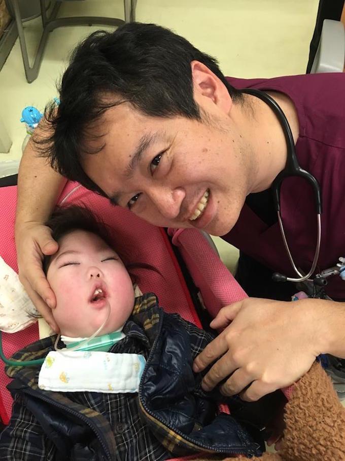 【写真】口から医療のための管をつないでいる子どもを、しまづともゆきさんが診療している