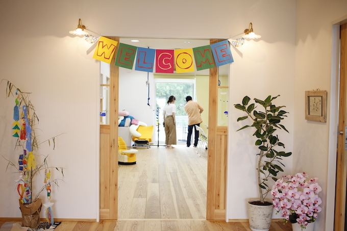 【写真】訪問介護ステーション内は白を基調とした清潔な壁に、木の温もりが感じられるドアが。そしてウェルカムと書かれた旗が飾られている
