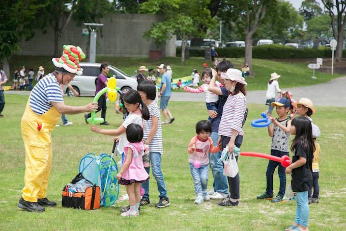 【写真】芝生にたくさんの親子が集まり、バルーンを受け取っている