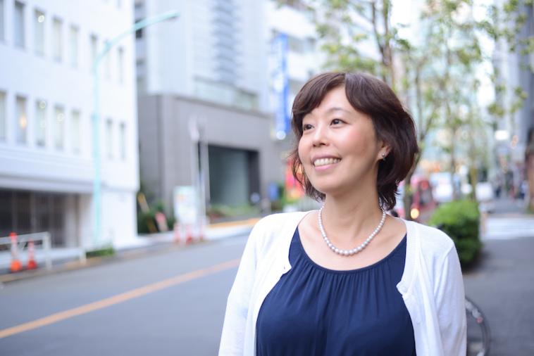 【写真】街頭に立ち遠くを見ながら微笑むよしおかゆうみさん
