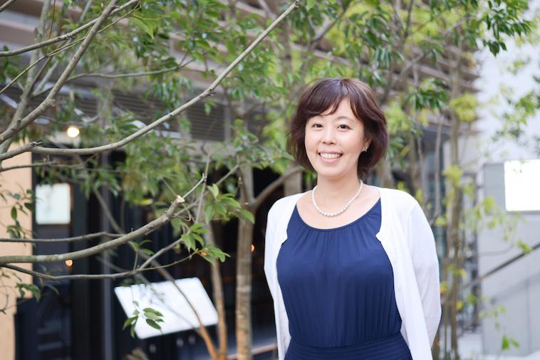 【写真】緑の木々の前に立ち微笑むよしおかゆうみさん
