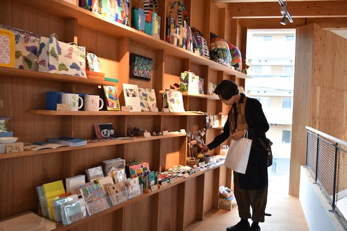 【写真】訪れた人が飾られているマグカップや鞄などのプロダクトを手に取り見つめている