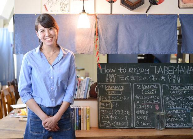 【写真】たべまなの看板の横で微笑むまりかさん