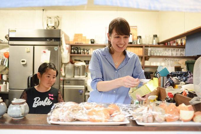 【写真】料理の準備をするまりかさんと興味ありげに覗き込む女の子
