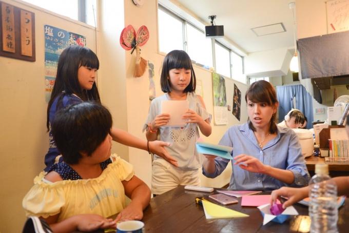 【写真】まりかさんと折り紙をする子どもたち