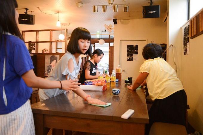 【写真】机を拭いて夕食の準備をする子どもたち