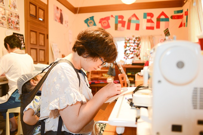 【写真】子どもを背負いながら裁縫をするメンバー