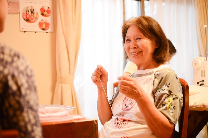 【写真】笑顔で裁縫をするたむらさん