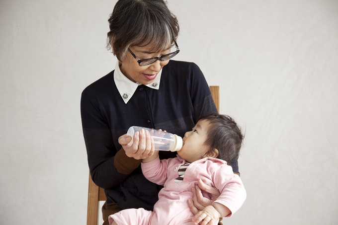 【写真】ばばらぼの商品の哺乳瓶で赤ちゃんにミルクをあげるメンバー