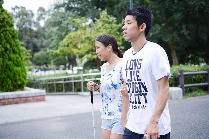 【写真】白杖を持って歩くちあきさんと腕で支えるゆうじさん