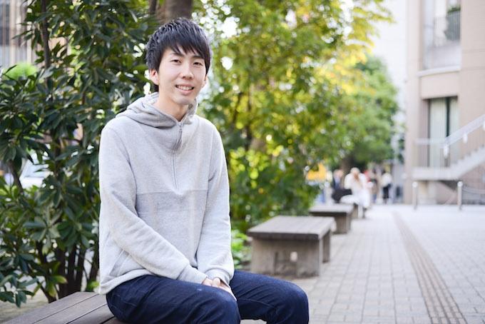 【写真】街頭のベンチに座り微笑んでいるまつおかそうしさん