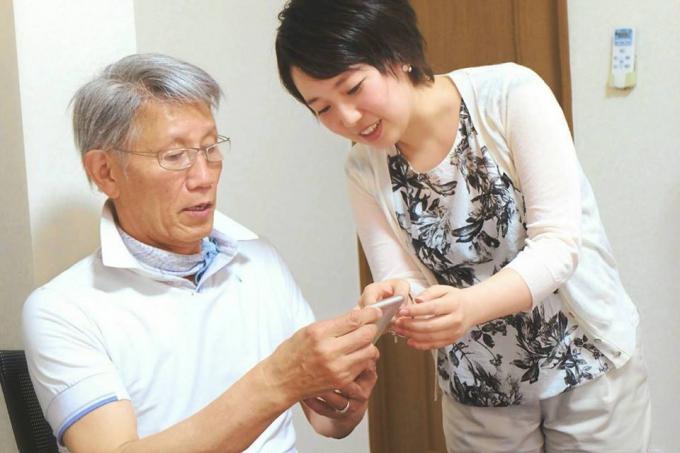 【写真】ごようききスタッフのいがらしさん。ある利用者にスマートフォンの使い方を教えている。