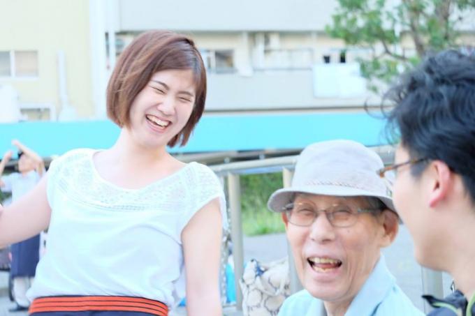 【写真】団地のおじいちゃんと一緒に笑っている学生スタッフ。2人とも楽しそうだ。
