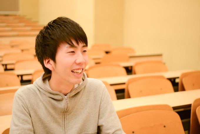 【写真】大学の講義室で笑顔で話すまつおかそうしさん