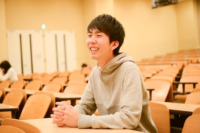 【写真】大学の講義室で笑顔にで話すまつおかそうしさん