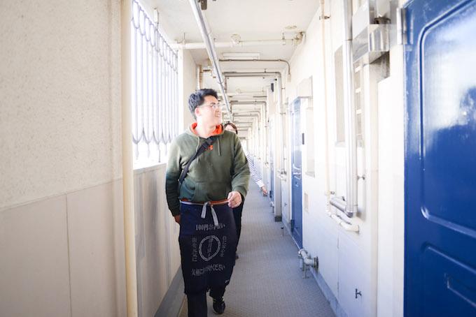【写真】団地内の廊下を歩きお客さんのもとに向かうまつおかさん。なんだか楽しそうだ。