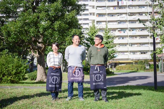 【写真】団地の一角にある公園。ごようききのスタッフ3人が笑みを浮かべながら立っている。
