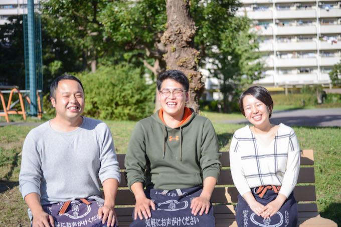 【写真】団地の一角にある公園。ごようききのスタッフ3人が笑みを浮かべながらベンチに座っている。
