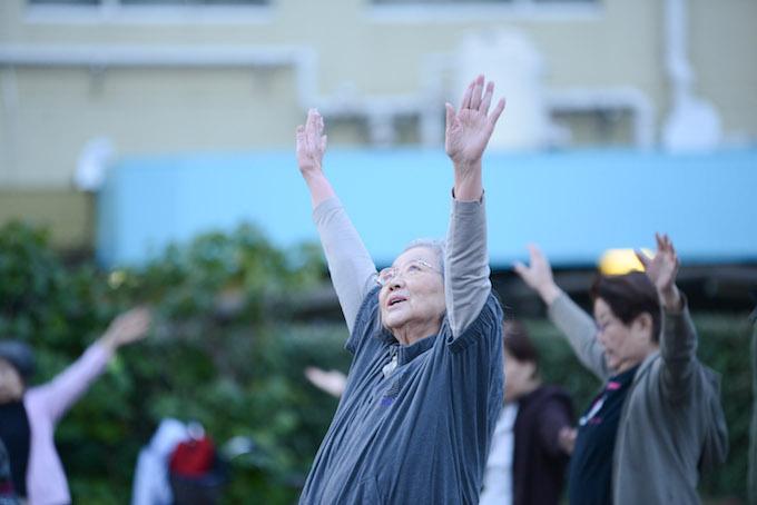 【写真】ちぃちゃん体操をしている参加者。手を空に伸ばす。表情ものびのびしている。