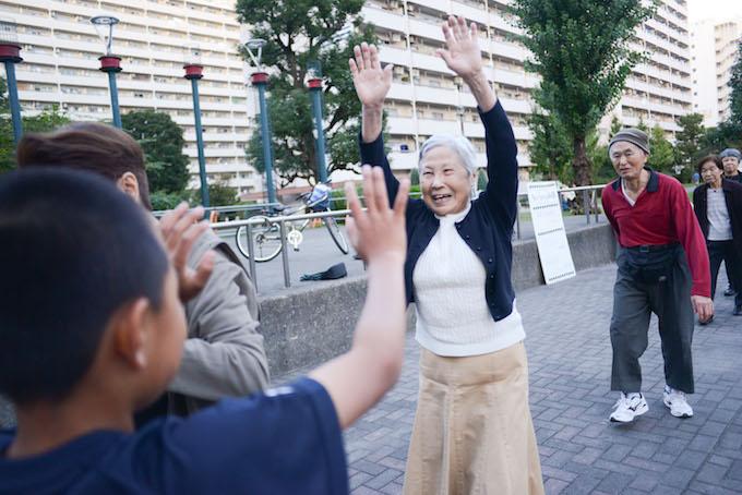 【写真】お互いにハイタッチするちぃちゃん体操の参加者たち。世代関係なく、楽しそうに交流している。