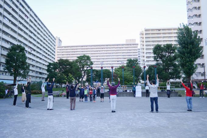【写真】団地内の公園で円を作り、体操をしている団地のみなさん。高齢者からこどもまで十数人が集まっている。