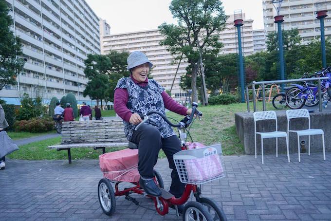 【写真】自転車に乗りながら楽しそうにインタビューに応えるちぃちゃん体操の参加者。
