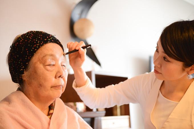 【写真】おばあさまにメイクを施すちしおさん。おばあさまは、安心した表情で目を瞑っている