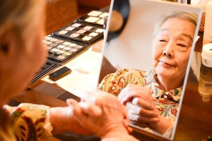【写真】メイクされた美しい顔を、鏡で眺めながら微笑むおばあさま