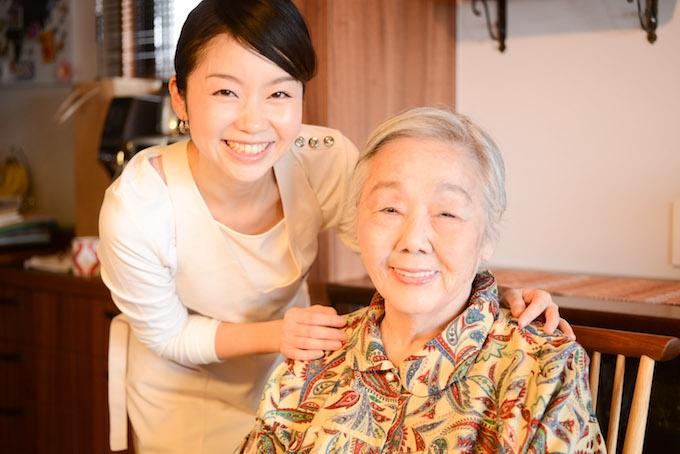 【写真】メイクが完了したおばあさまの肩に手を置き、笑顔でカメラを見つめるちしおさん