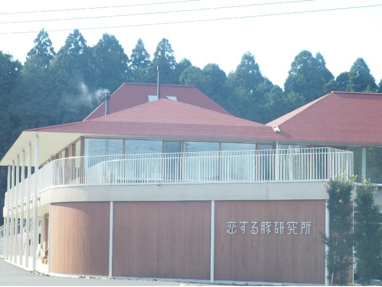 【写真】周囲の緑の中に溶け込むこいするぶたけんきゅうじょの建物。赤い屋根に茶色の壁で、温かい印象
